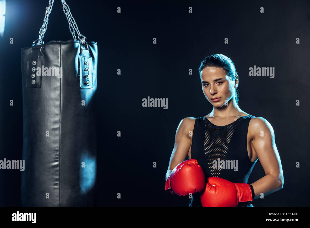 Strong boxer in red gloves standing near punching bag and looking at camera on black - Stock Image