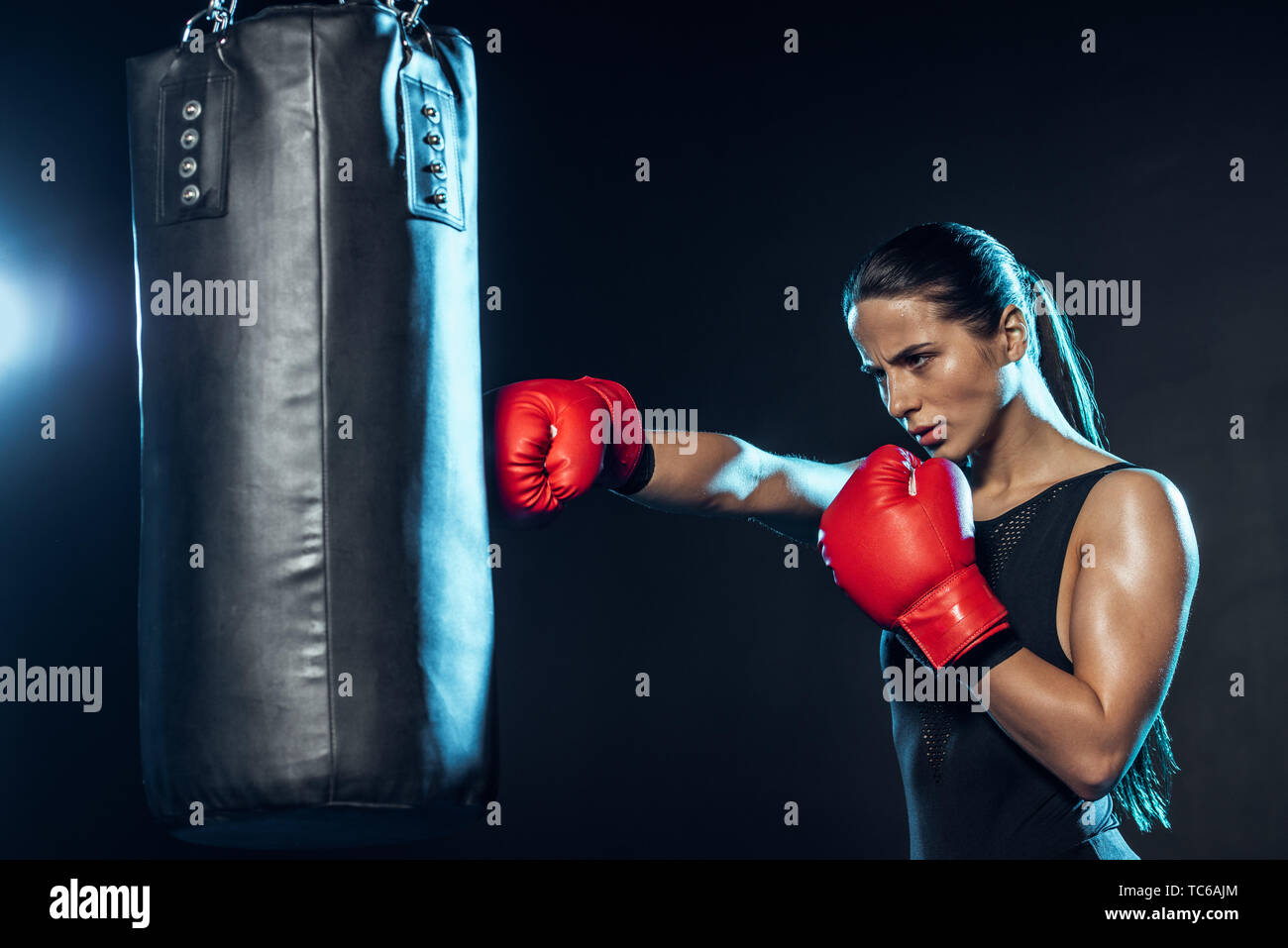 Tired boxer in red boxing gloves training with punching bag on black - Stock Image