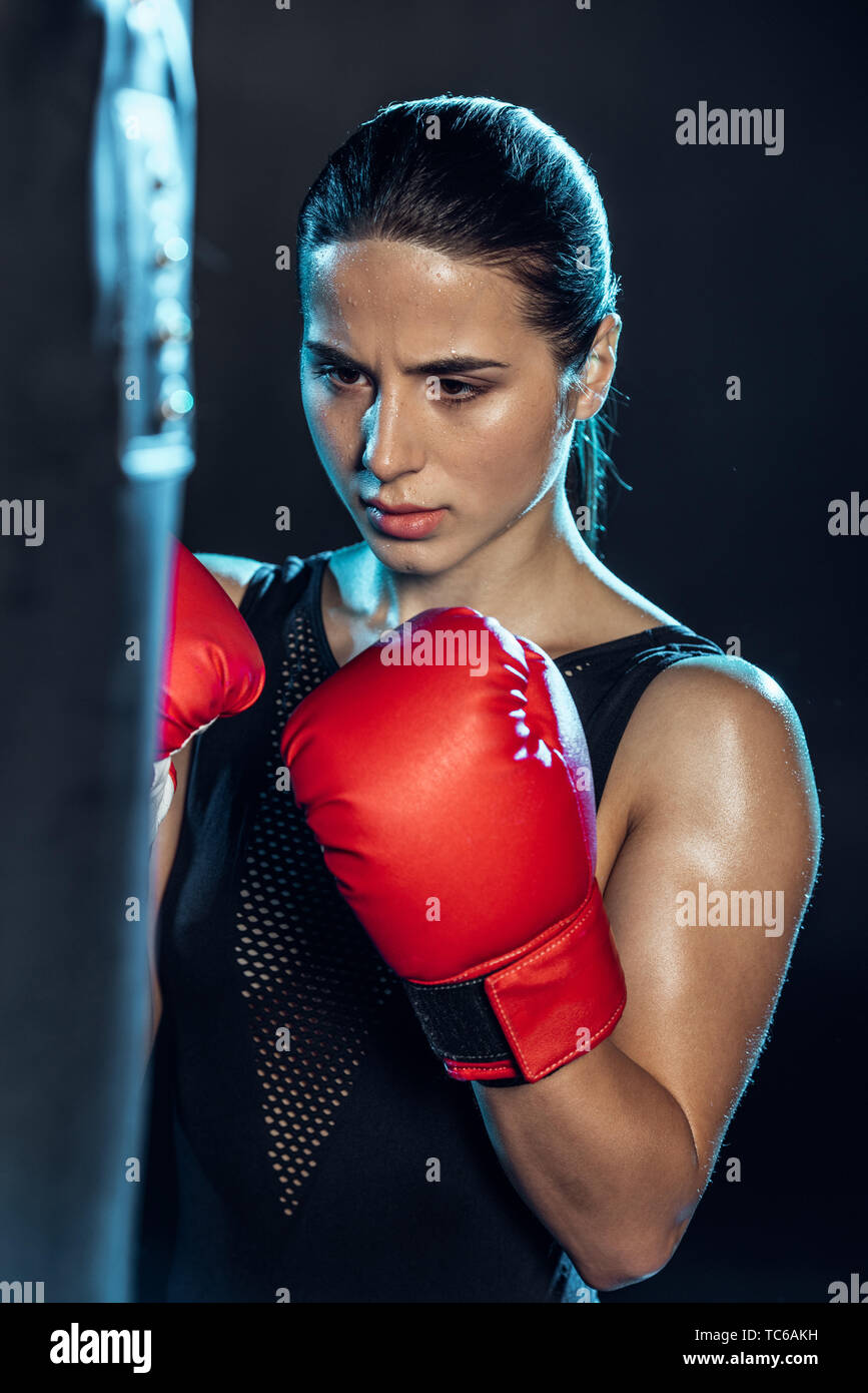 exhausted boxer in red gloves looking at punching bag on black - Stock Image