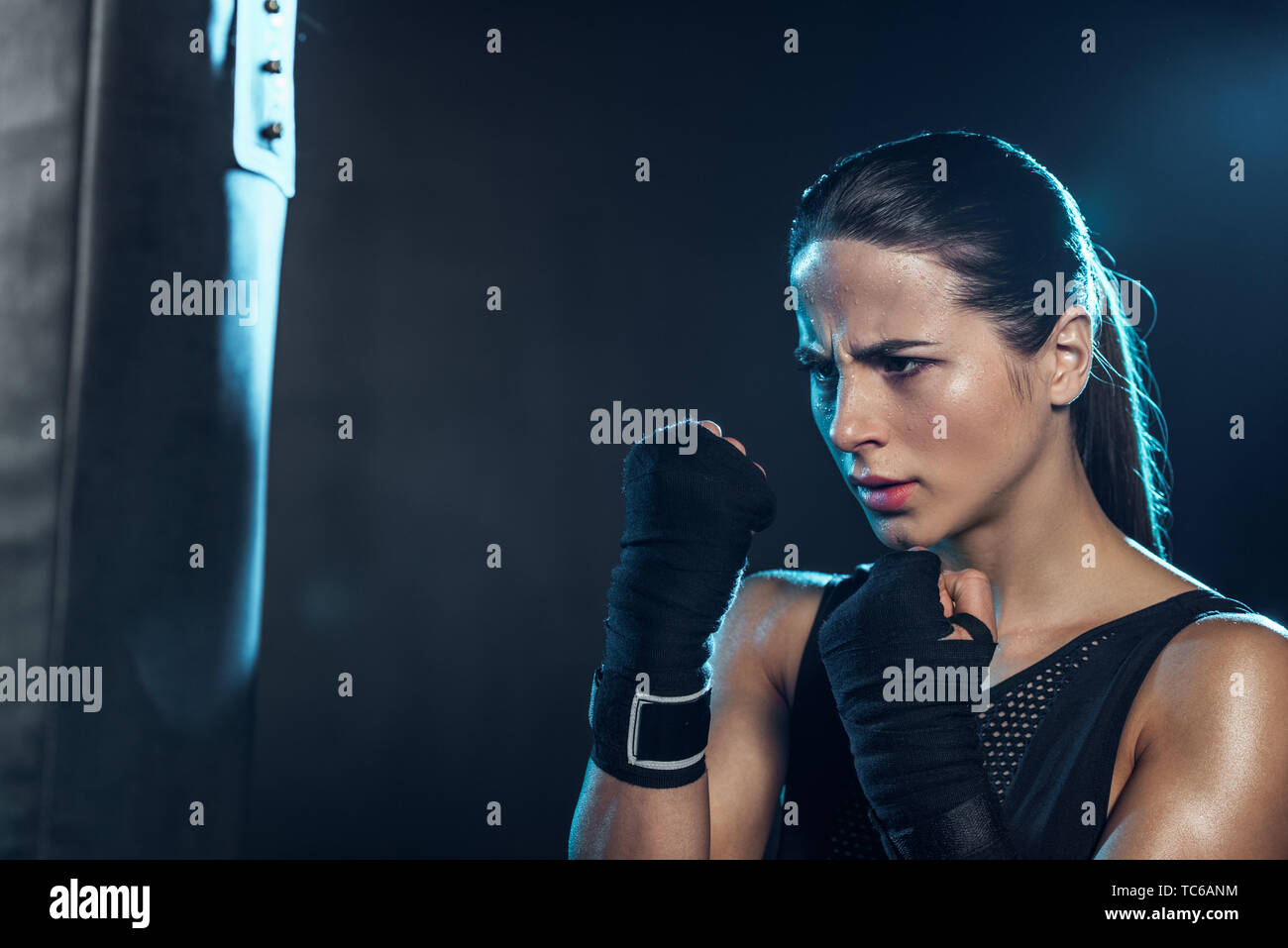 exhausted boxer in gloves looking at punching bag on black - Stock Image