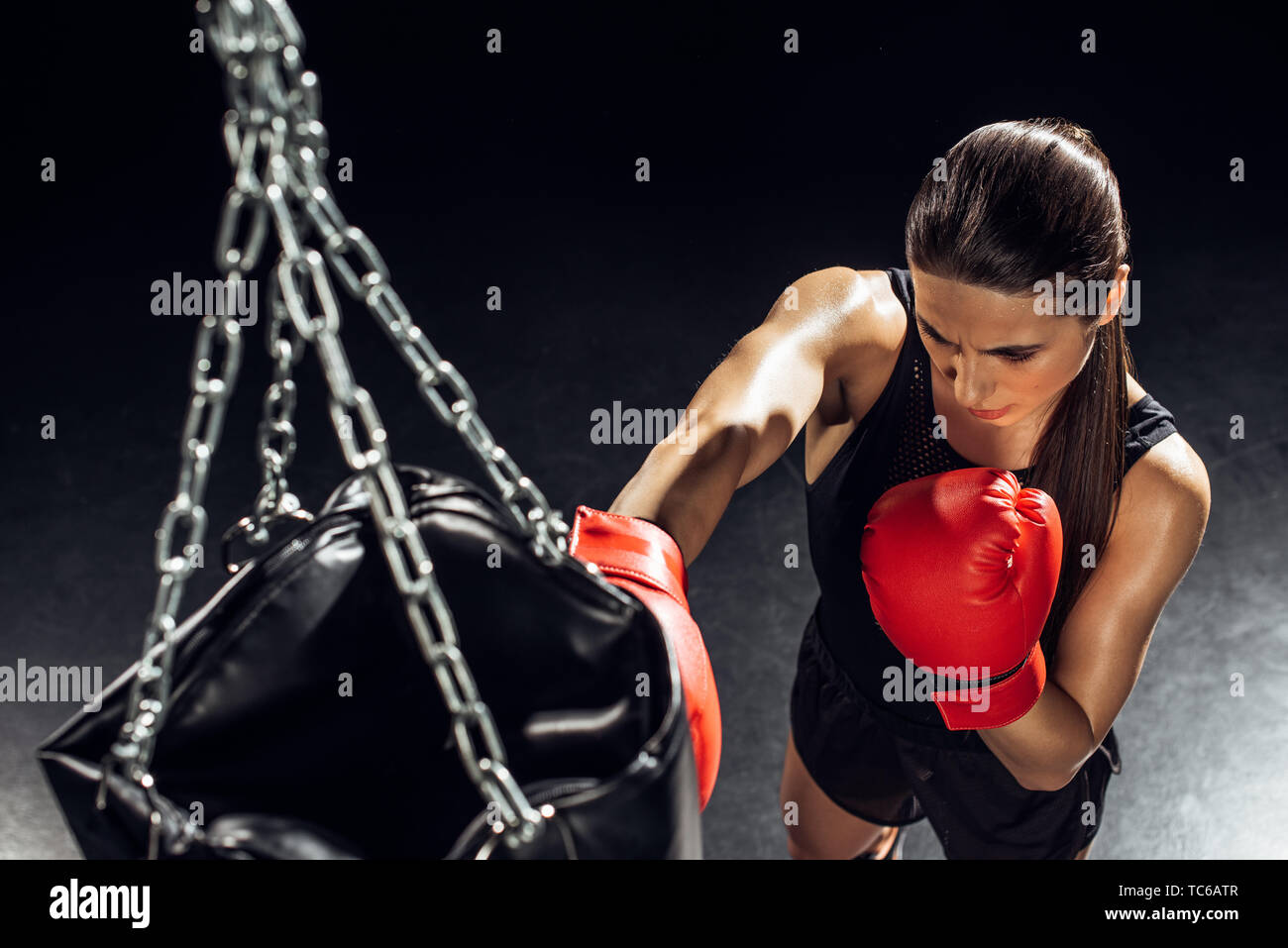 High angle view of boxer in red boxing gloves training with punching bag - Stock Image