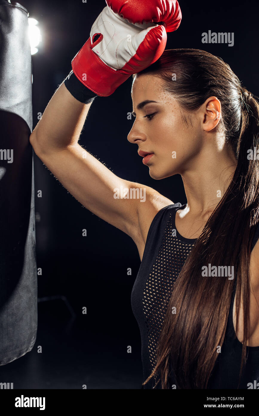 Tired boxer with ponytail standing near punching bag on black - Stock Image