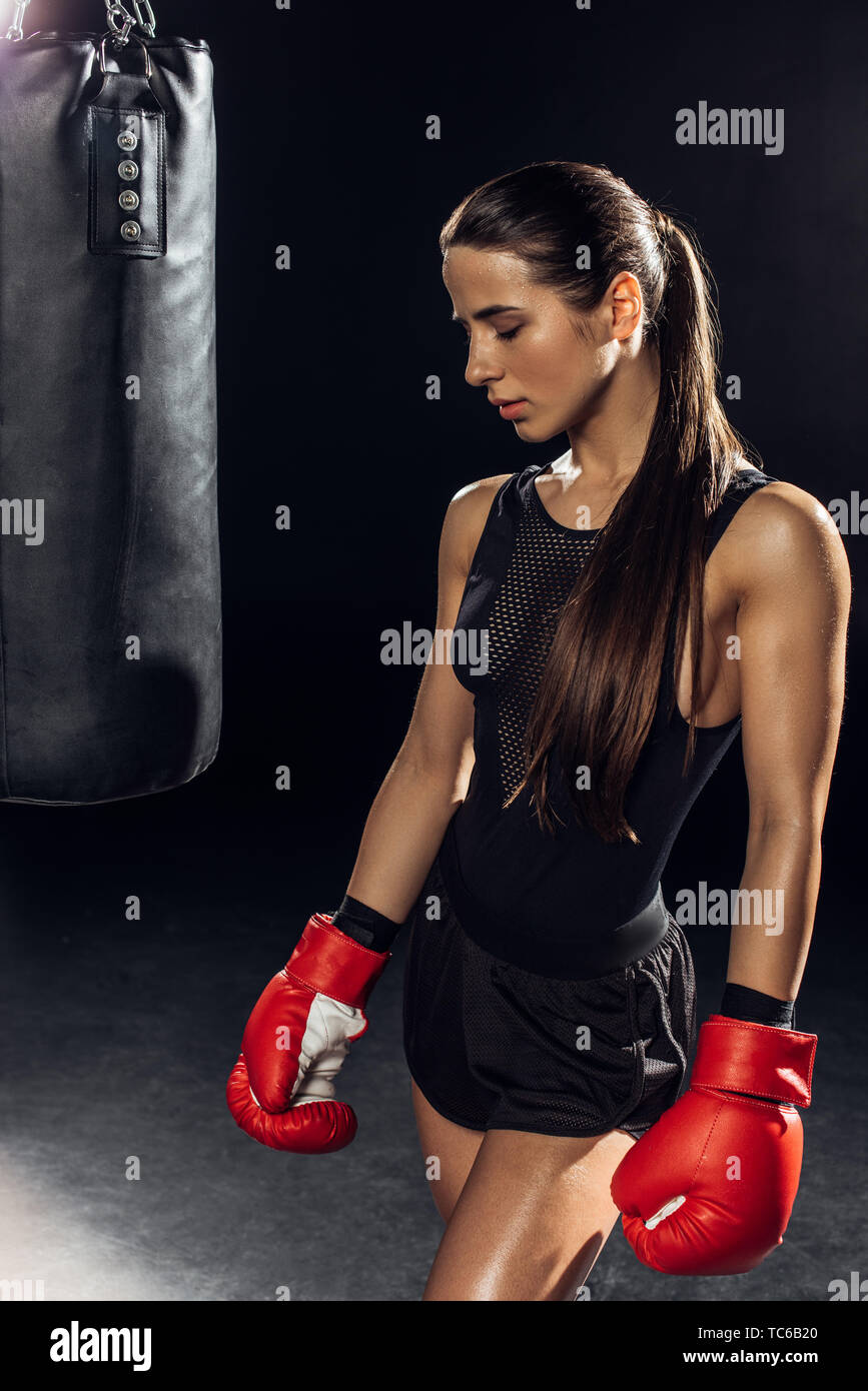 Female boxer in red boxing gloves standing near punching bag - Stock Image