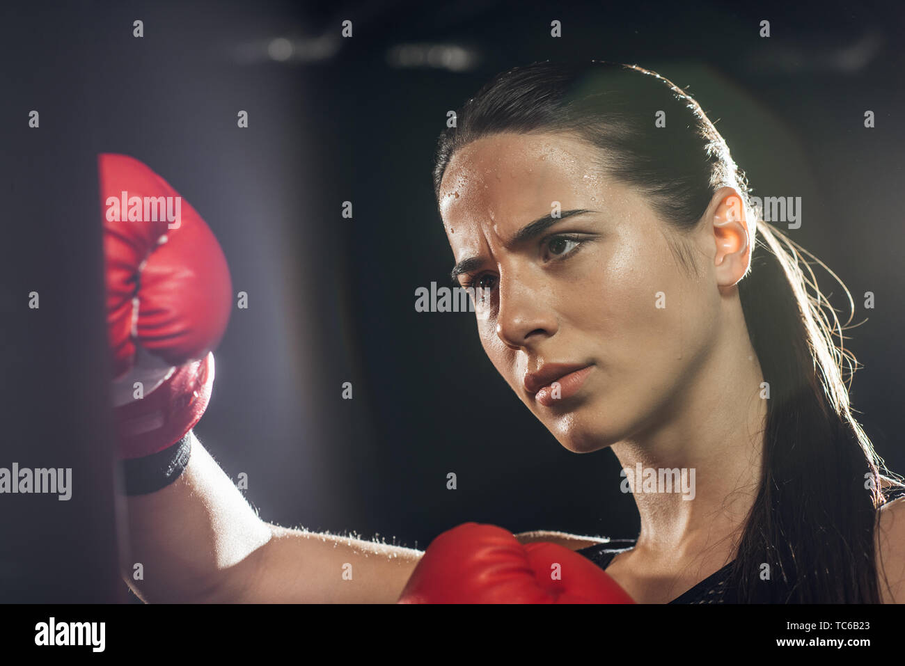 Selective focus of exhausted boxer training with punching bag on black - Stock Image