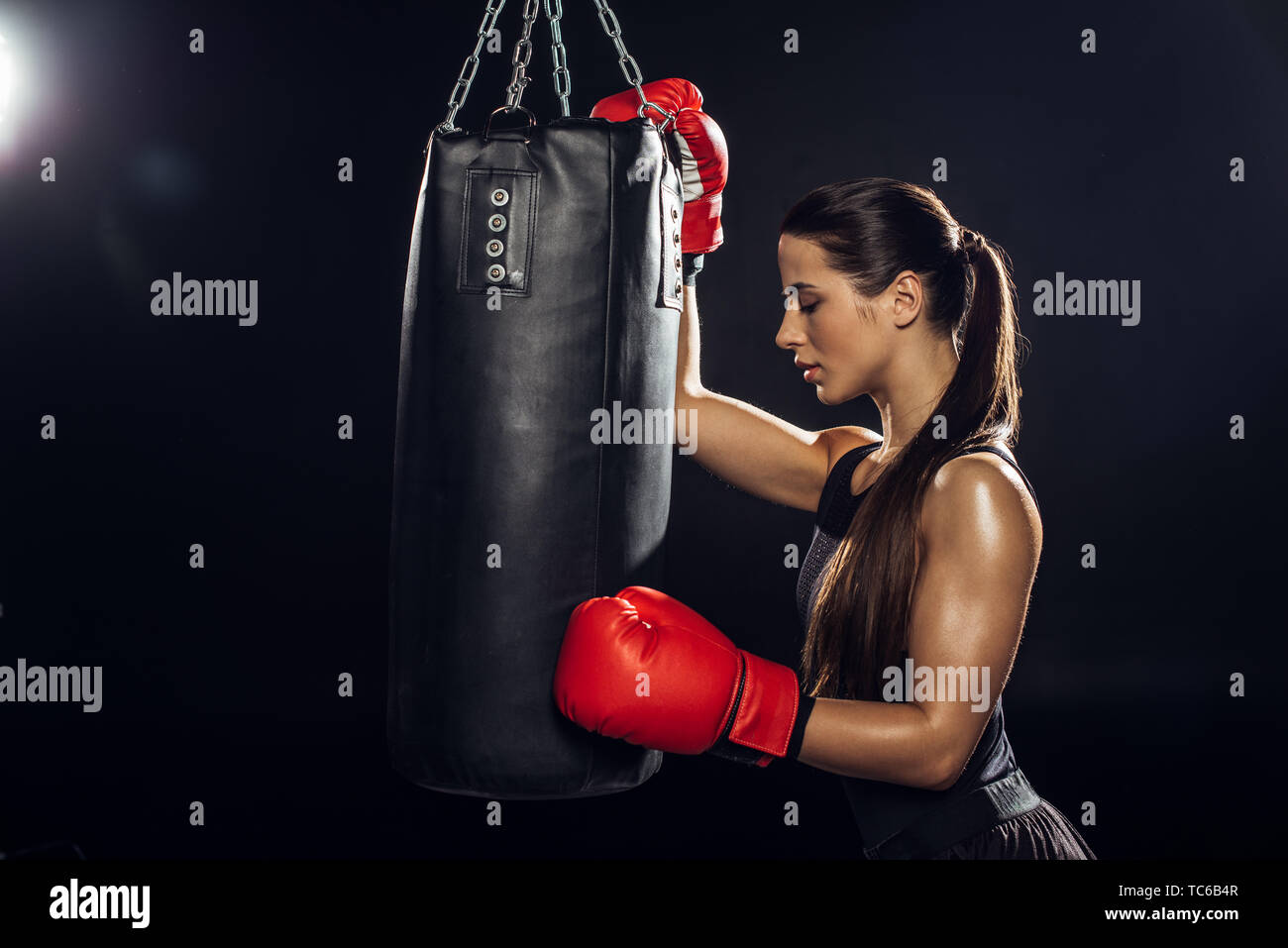 Side view of female boxer in red boxing gloves training with punching bag - Stock Image