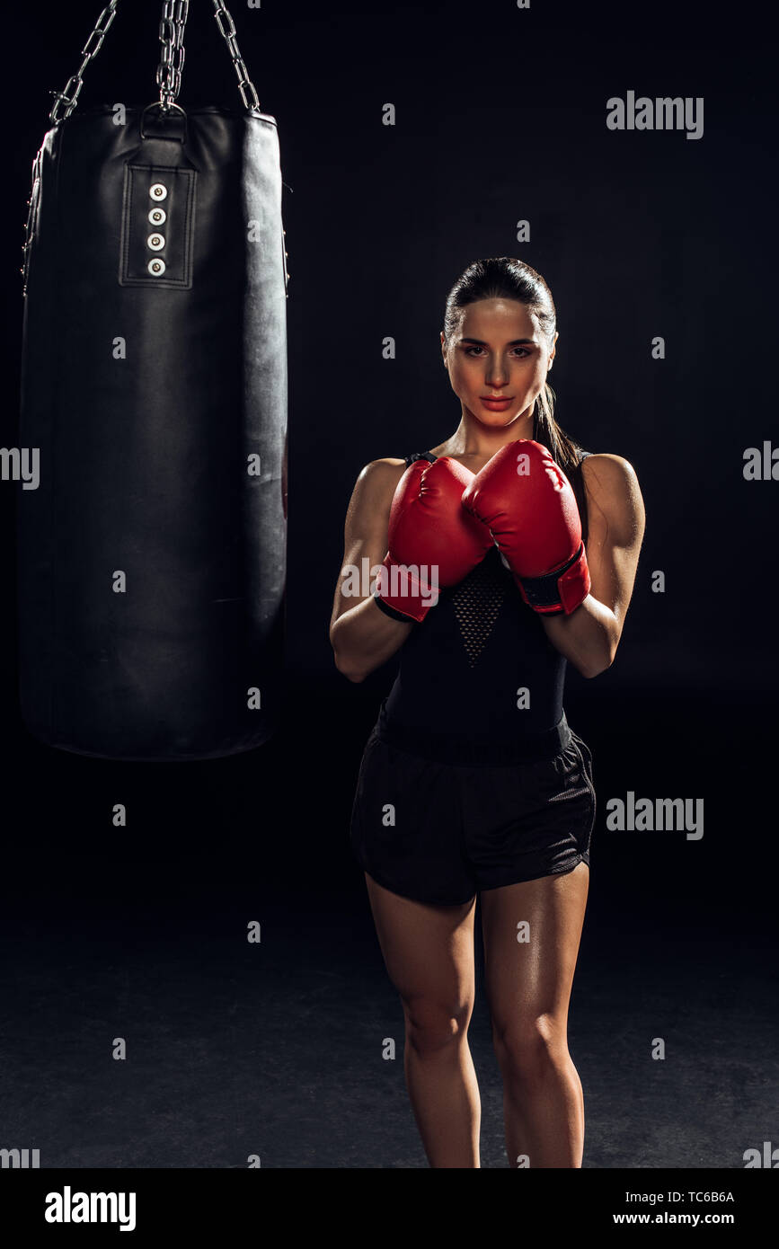 Front view of boxer in red boxing gloves standing near punching bag on black - Stock Image