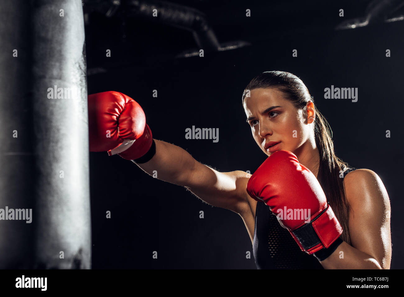 Female boxer in red boxing gloves training with punching bag - Stock Image