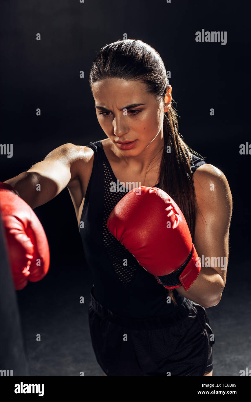 High angle view of tired boxer in red boxing gloves training with punching bag on black - Stock Image