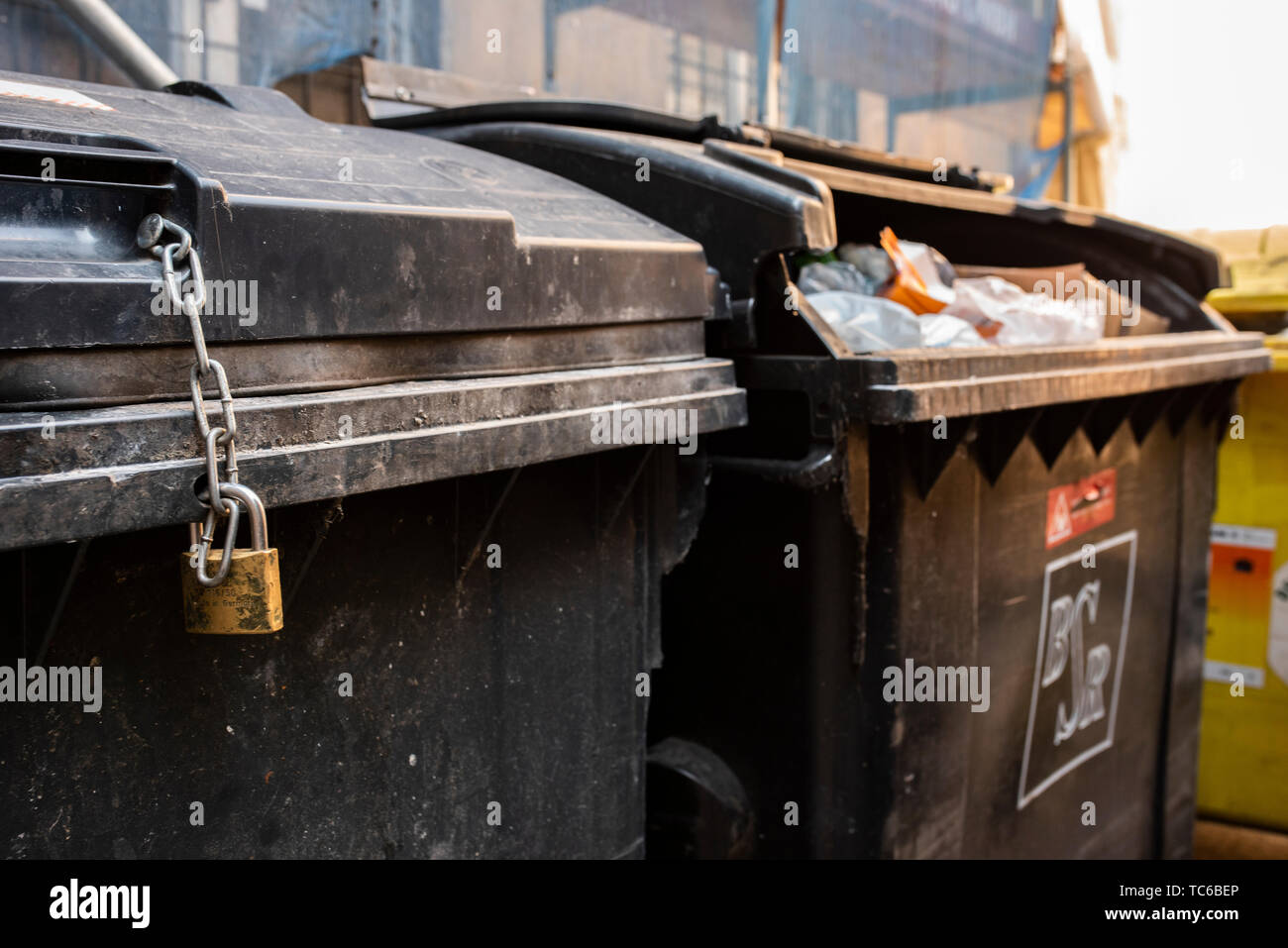 05 June 2019, Berlin: Two black garbage cans stand next to each other, one of them is locked with a chain lock. According to a study, Berlin is not exactly one of the cheapest cities in terms of waste disposal charges. Among the 100 largest cities in Germany, the capital thus ranks 68th (to dpa 'Städtevergleich: Berlins Müllgebühren im Mittelfeld'). Photo: Theresa Kottas-Heldenberg/dpa - Stock Image
