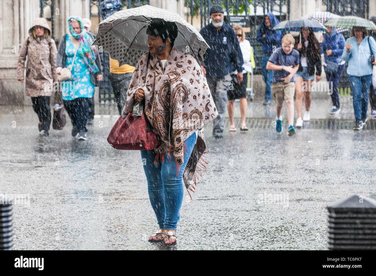 London, UK. 6 June, 2019. Members of the public seek shelter outside the Palace of Westminster during a sudden rain shower. Scattered showers are forecast for the remainder of the day, with heavy rain to follow tomorrow. Credit: Mark Kerrison/Alamy Live News - Stock Image