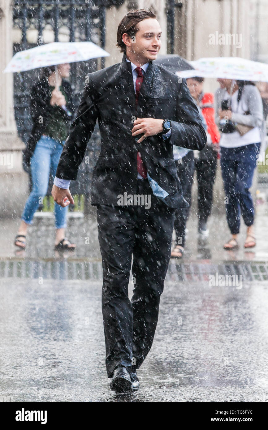 London, UK. 6 June, 2019. A man seeks shelter outside the Palace of Westminster during a sudden rain shower. Scattered showers are forecast for the remainder of the day, with heavy rain to follow tomorrow. Credit: Mark Kerrison/Alamy Live News - Stock Image