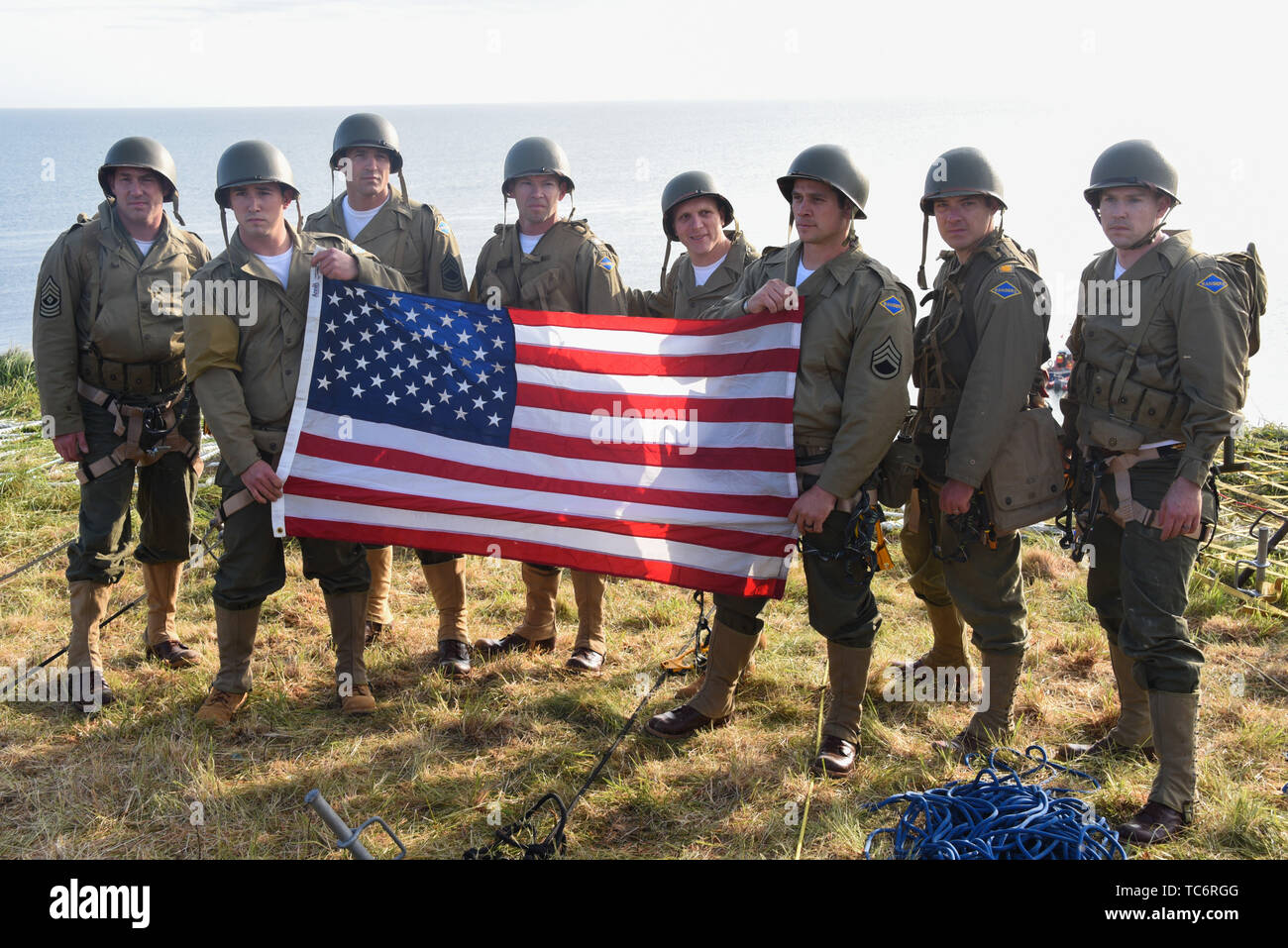Pointe Du Hoc, France. 05th June, 2019. U.S. Army soldiers with 75th Ranger Regiment hold up an American flag after they scaled the cliffs at Omaha Beach, re-enacting Operation Overload during the World War Two D-Day invasion June 5, 2019 in Pointe du Hoc, Normandy, France. Thousands have converged on Normandy to commemorate the 75th anniversary of Operation Overlord, the WWII Allied invasion commonly known as D-Day. Credit: Planetpix/Alamy Live News Stock Photo