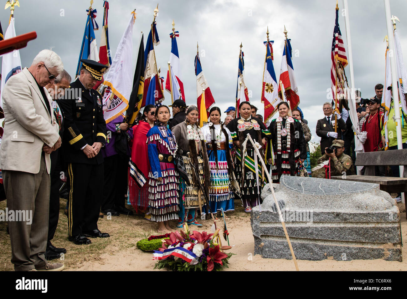 Pointe Du Hoc, France. 05th June, 2019. A moment of silence is honored for the fallen Native American WWII soldiers at the Charles Shay memorial ceremony at Omaha Beach on the anniversary of the D-Day invasion June 5, 2019 in Pointe du Hoc, Normandy, France. Thousands have converged on Normandy to commemorate the 75th anniversary of Operation Overlord, the WWII Allied invasion commonly known as D-Day. Credit: Planetpix/Alamy Live News Stock Photo