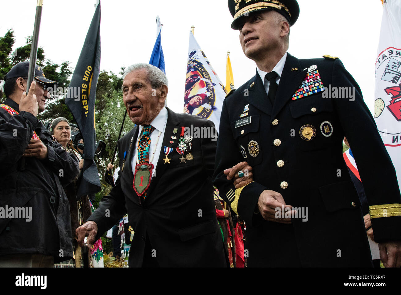 Pointe Du Hoc, France. 05th June, 2019. U.S. Gen. Paul M. Nakasone, commander of Cyber Command, right, escorts Native American WWII veteran Charles Shay to the Charles Shay memorial ceremony at Omaha Beach on the anniversary of the D-Day invasion June 5, 2019 in Pointe du Hoc, Normandy, France. Thousands have converged on Normandy to commemorate the 75th anniversary of Operation Overlord, the WWII Allied invasion commonly known as D-Day. Credit: Planetpix/Alamy Live News Stock Photo
