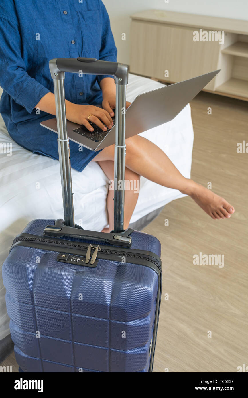 Office woman working on laptop next to suitcase - Stock Image