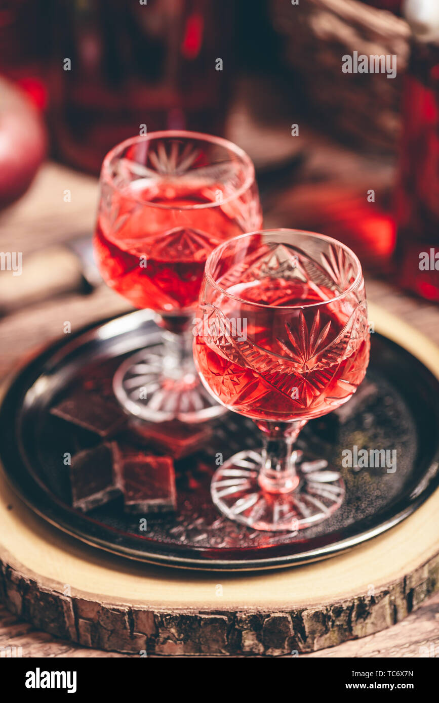 Homemade red currant nalivka and chocolate on metal tray - Stock Image