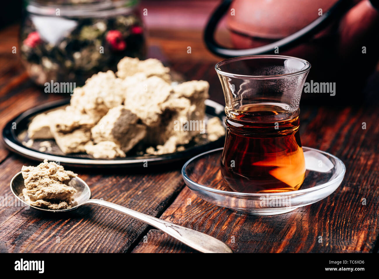 Black tea in armudu glass and spoonful of sunflower halva - Stock Image