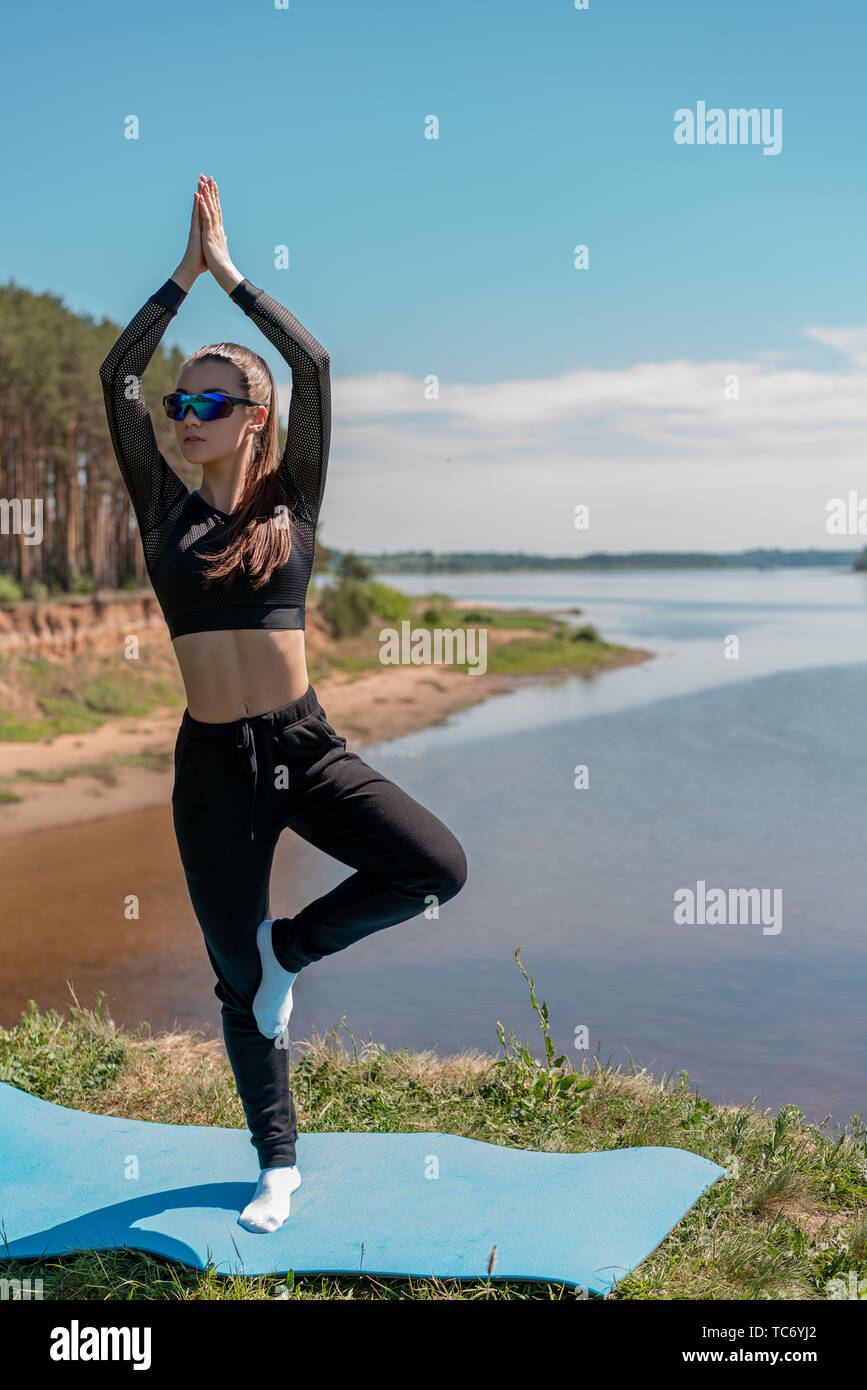 girl in sport uniform and sunglasses doing yoga on the bank of the river. Healthy lifestyle - Stock Image