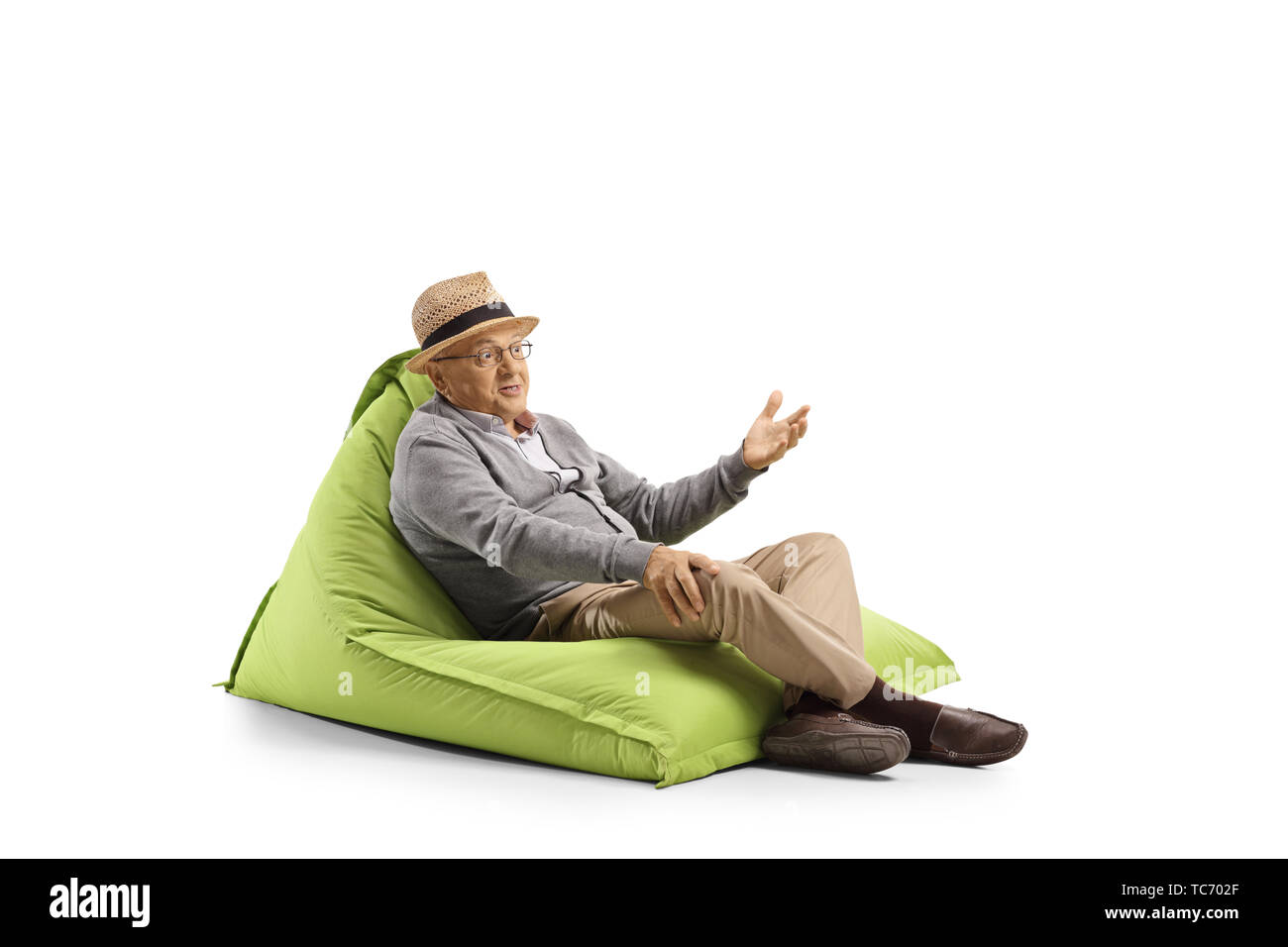 Senior man with face expression resting on a bean-bag armchair and gesturing with hand isolated on white background - Stock Image