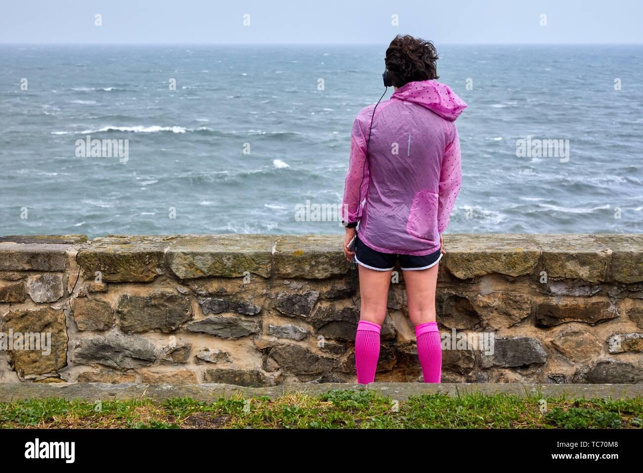 Woman doing sport looking at the sea, Paseo Nuevo, Donostia, San Sebastian, Gipuzkoa, Basque Country, Spain Stock Photo