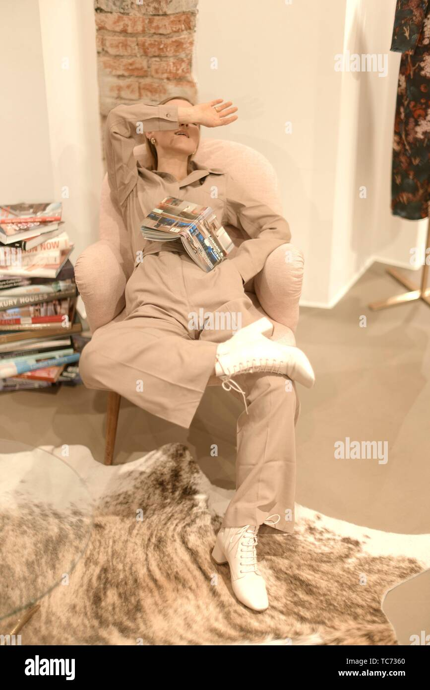 tired fashionable woman resting indoors on chair, exhausted, wearing cool stylish one piece jumpsuit, beige trend outfit, women´s fashion jumper, - Stock Image