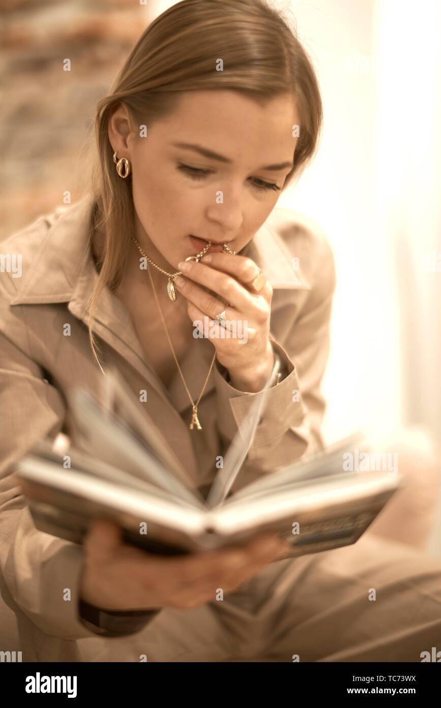 fashionable blogger woman reading book indoors, wearing individual jewellery necklace chain with custom made letter A representing the first letter - Stock Image