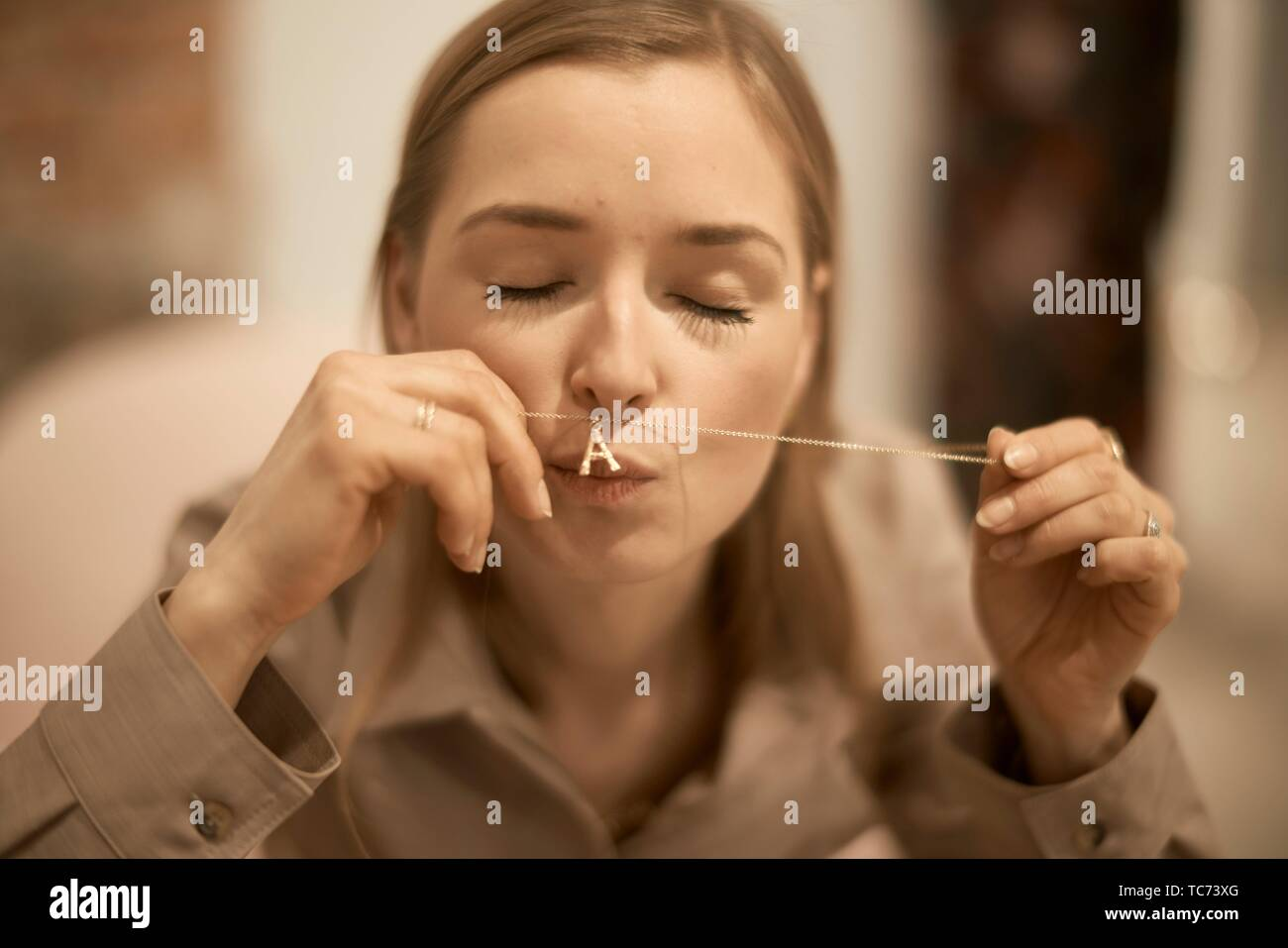 rich woman kissing women´s jewellery necklace chain accessory with custom made letter A representing first letter of her personal name Anna, - Stock Image