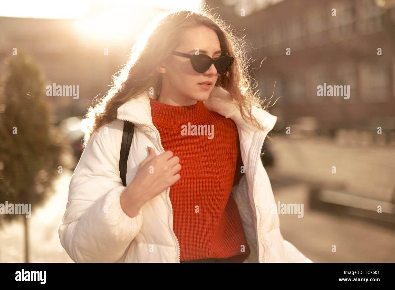 young stylish woman wearing sunglasses, upper body shot, in city Cottbus, Brandenburg, Germany. - Stock Image