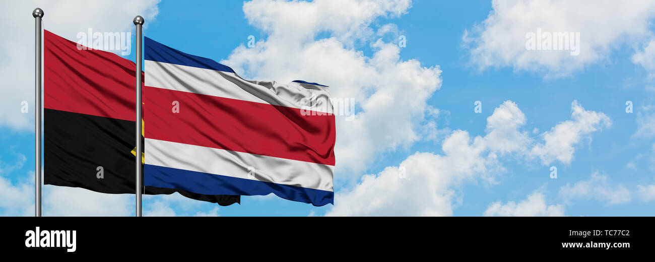 Angola and Costa Rica flag waving in the wind against white cloudy blue sky together. Diplomacy concept, international relations. - Stock Image
