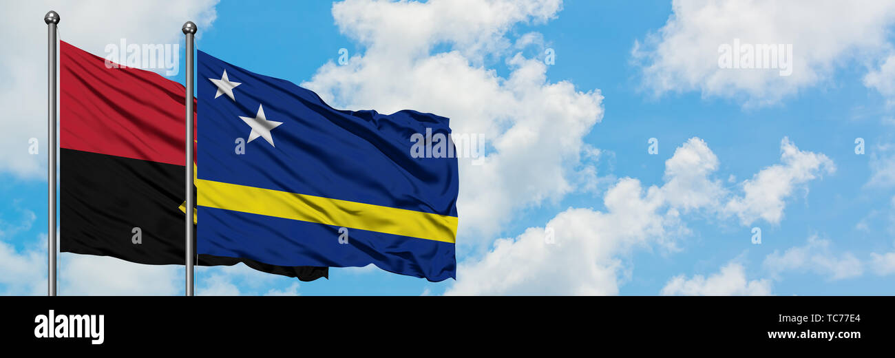 Angola and Curacao flag waving in the wind against white cloudy blue sky together. Diplomacy concept, international relations. - Stock Image