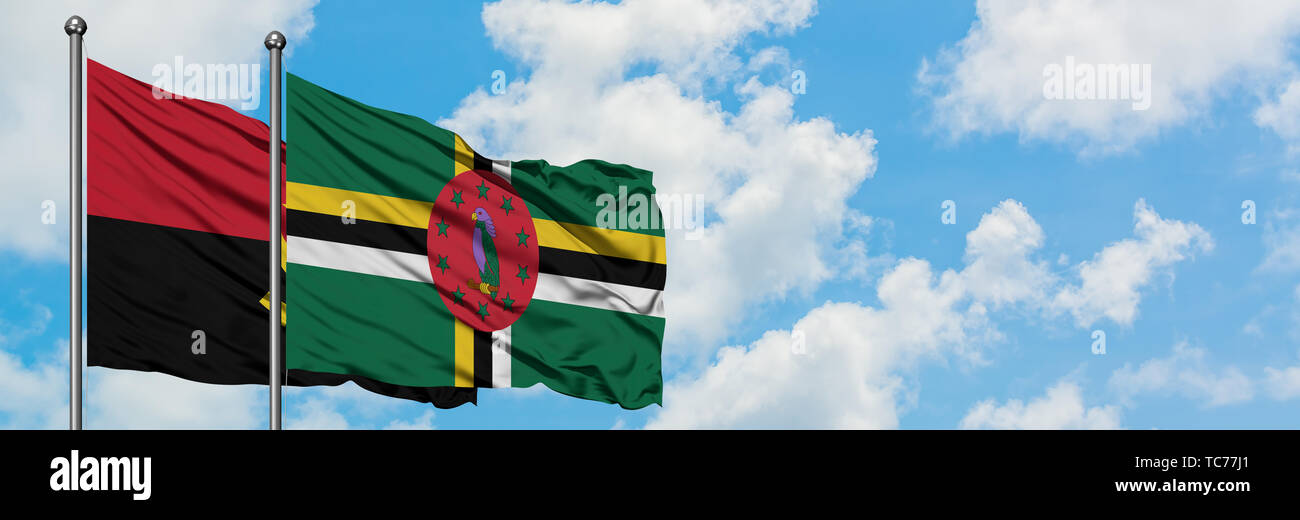 Angola and Dominica flag waving in the wind against white cloudy blue sky together. Diplomacy concept, international relations. - Stock Image