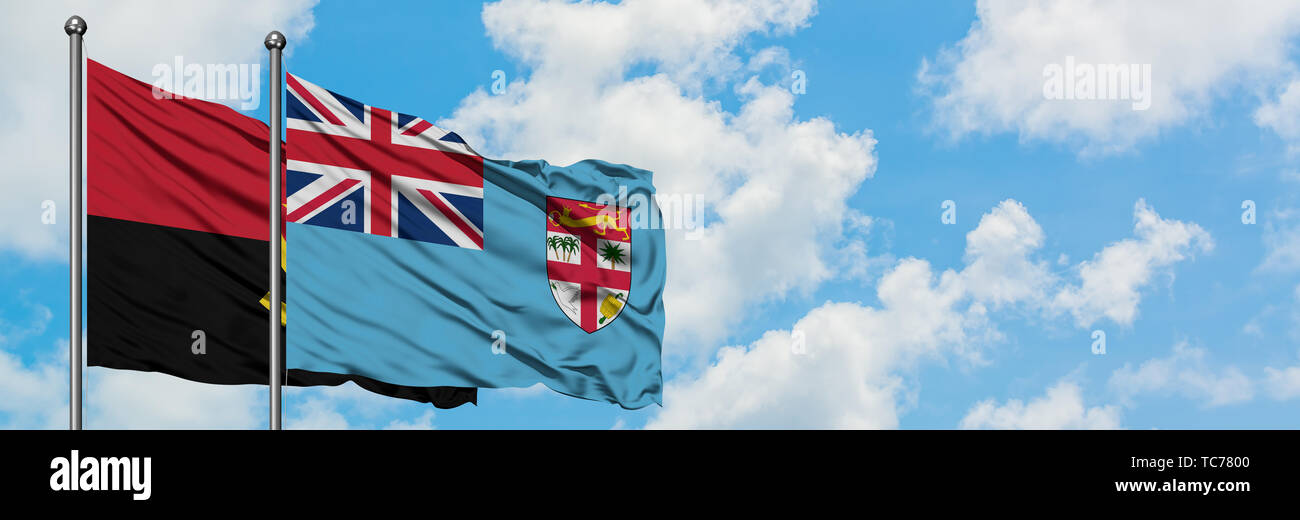 Angola and Fiji flag waving in the wind against white cloudy blue sky together. Diplomacy concept, international relations. - Stock Image