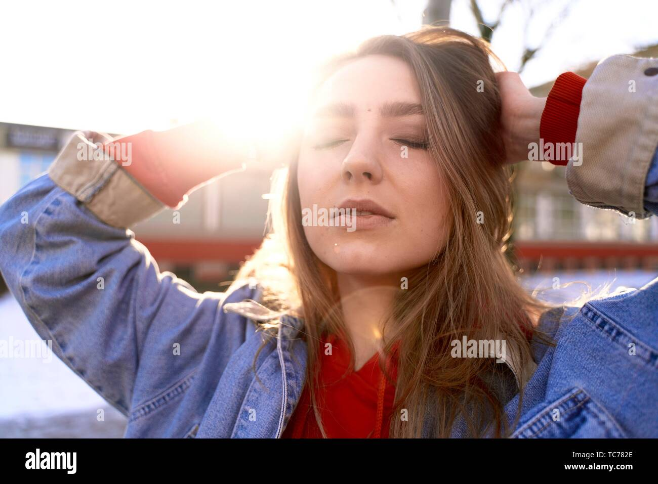 young emotive woman with closed eyes outdoors sunlight, in Cottbus, Brandenburg, Germany - Stock Image