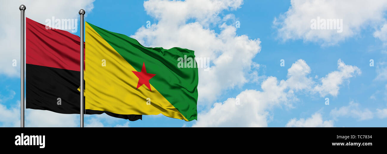 Angola and French Guiana flag waving in the wind against white cloudy blue sky together. Diplomacy concept, international relations. - Stock Image