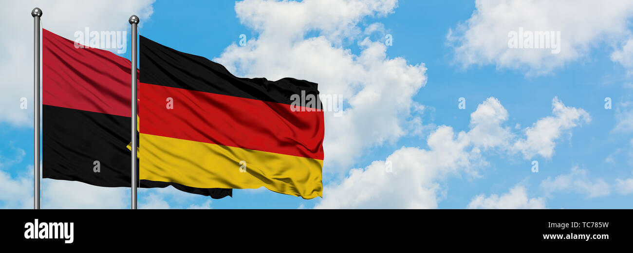 Angola and Germany flag waving in the wind against white cloudy blue sky together. Diplomacy concept, international relations. - Stock Image