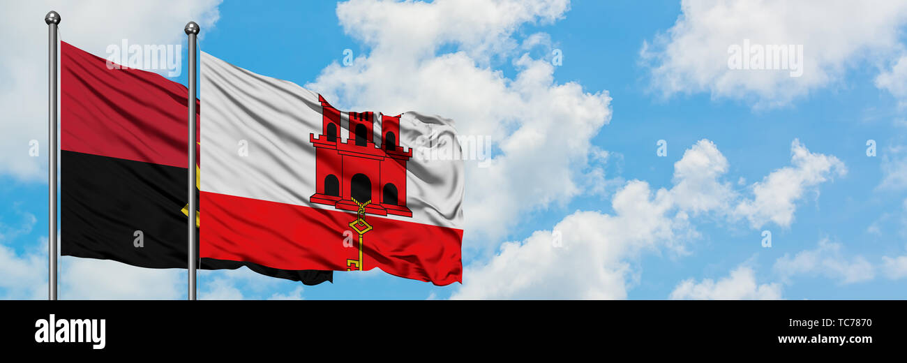 Angola and Gibraltar flag waving in the wind against white cloudy blue sky together. Diplomacy concept, international relations. - Stock Image
