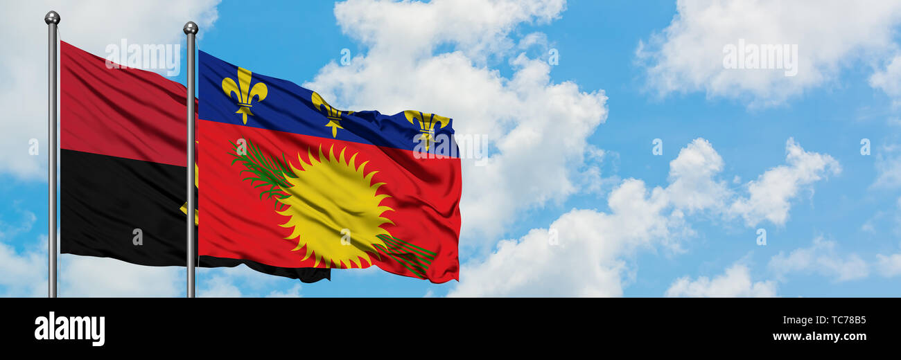 Angola and Guadeloupe flag waving in the wind against white cloudy blue sky together. Diplomacy concept, international relations. - Stock Image