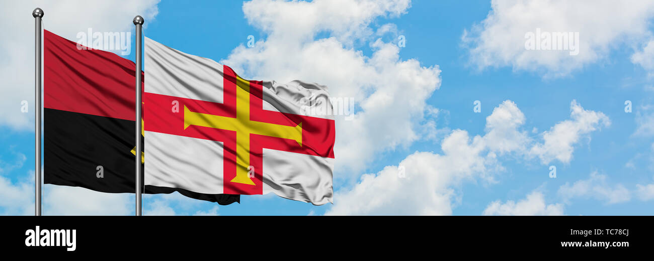 Angola and Guernsey flag waving in the wind against white cloudy blue sky together. Diplomacy concept, international relations. - Stock Image