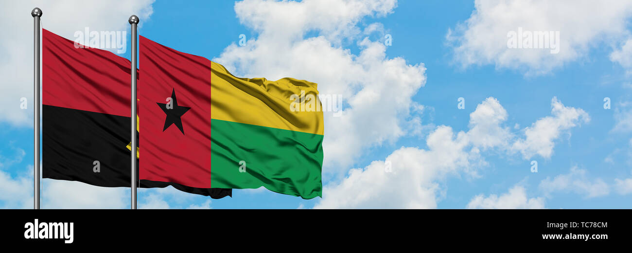 Angola and Guinea Bissau flag waving in the wind against white cloudy blue sky together. Diplomacy concept, international relations. - Stock Image