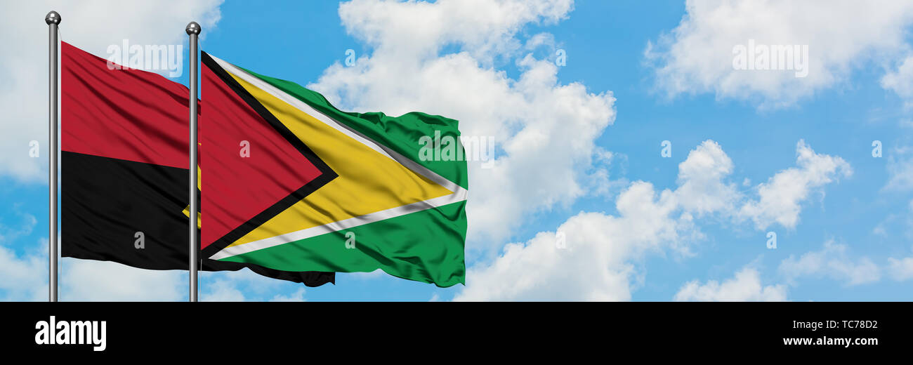 Angola and Guyana flag waving in the wind against white cloudy blue sky together. Diplomacy concept, international relations. - Stock Image