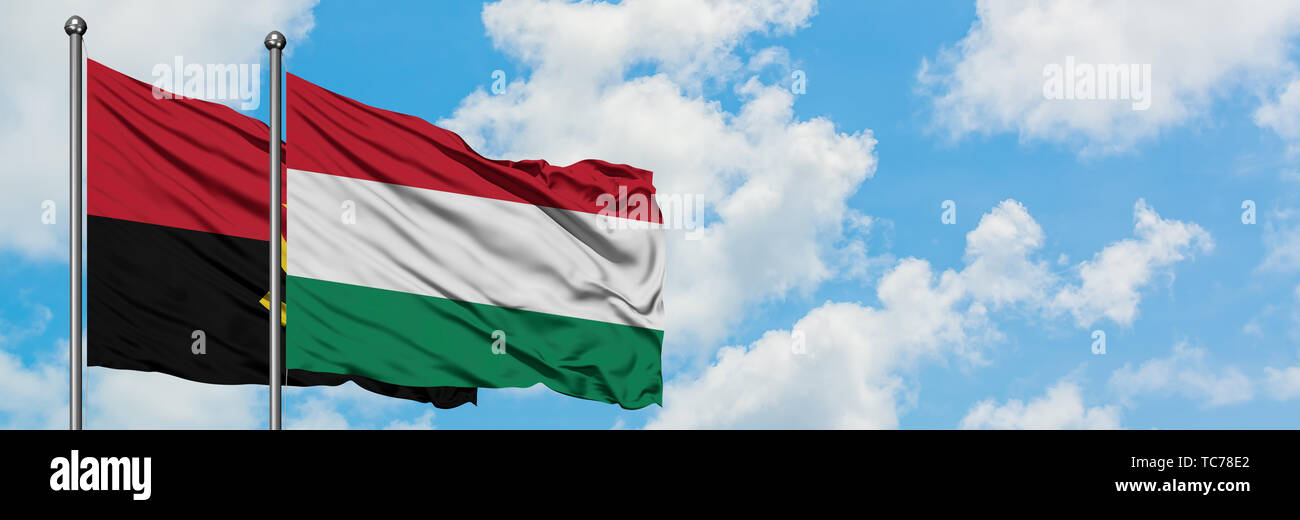 Angola and Hungary flag waving in the wind against white cloudy blue sky together. Diplomacy concept, international relations. - Stock Image