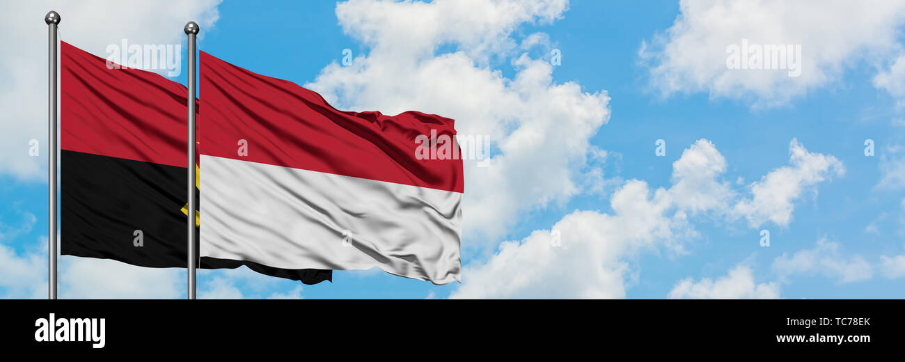 Angola and Indonesia flag waving in the wind against white cloudy blue sky together. Diplomacy concept, international relations. - Stock Image
