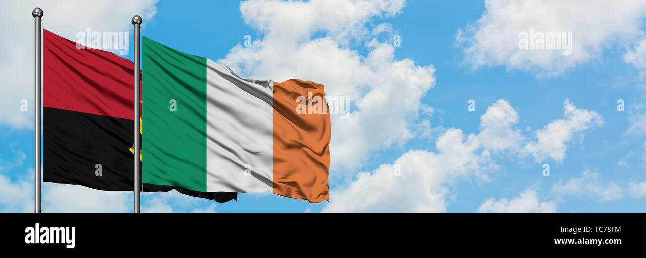 Angola and Ireland flag waving in the wind against white cloudy blue sky together. Diplomacy concept, international relations. - Stock Image