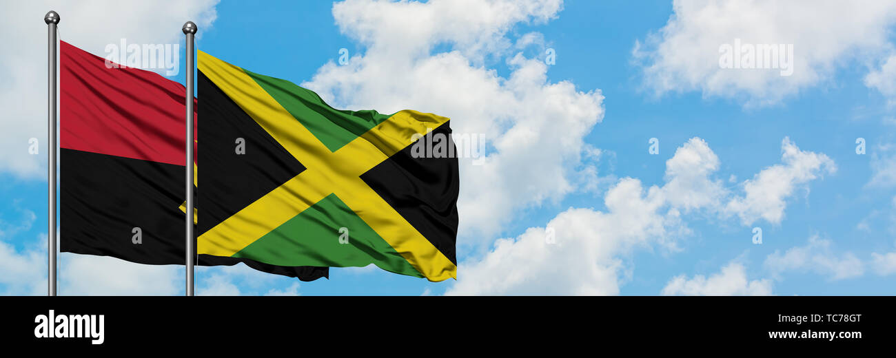 Angola and Jamaica flag waving in the wind against white cloudy blue sky together. Diplomacy concept, international relations. - Stock Image