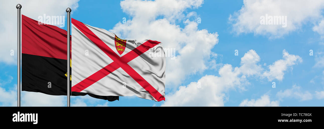 Angola and Jersey flag waving in the wind against white cloudy blue sky together. Diplomacy concept, international relations. - Stock Image