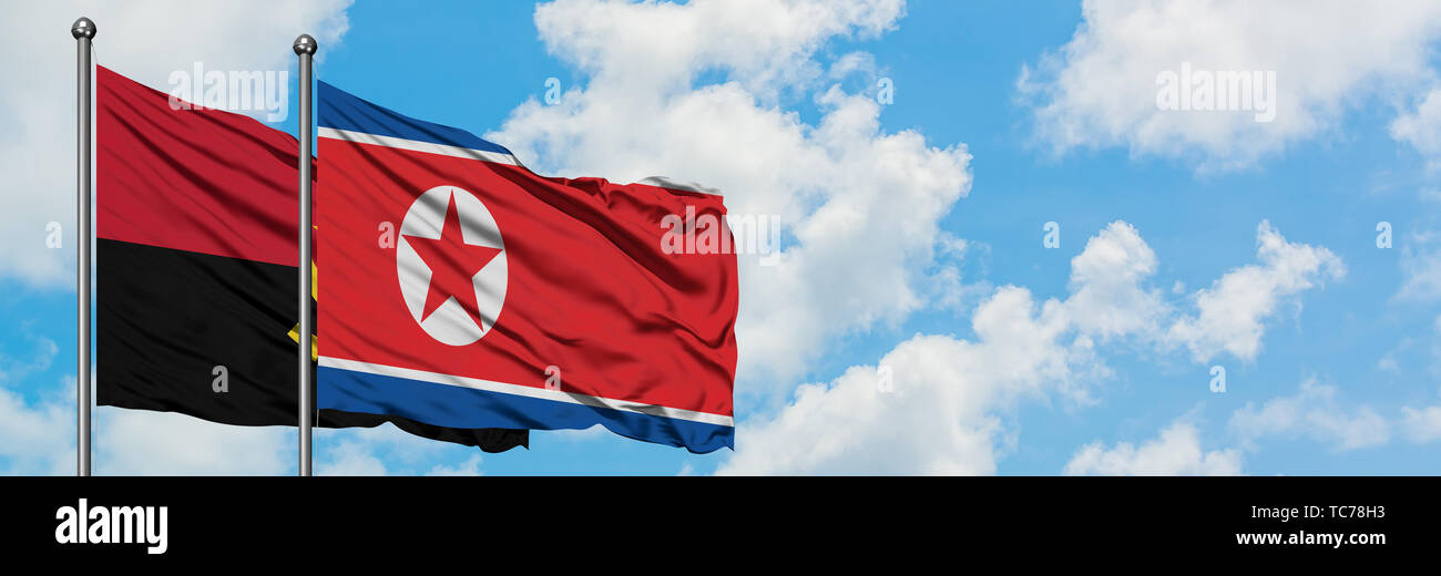 Angola and North Korea flag waving in the wind against white cloudy blue sky together. Diplomacy concept, international relations. - Stock Image