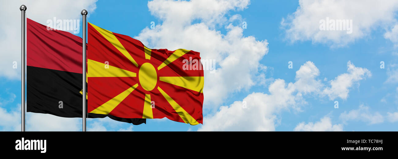 Angola and Macedonia flag waving in the wind against white cloudy blue sky together. Diplomacy concept, international relations. - Stock Image