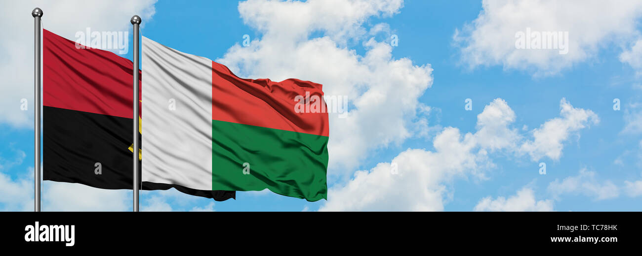 Angola and Madagascar flag waving in the wind against white cloudy blue sky together. Diplomacy concept, international relations. - Stock Image