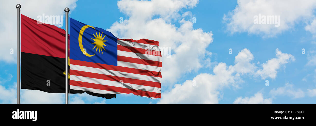 Angola and Malaysia flag waving in the wind against white cloudy blue sky together. Diplomacy concept, international relations. - Stock Image