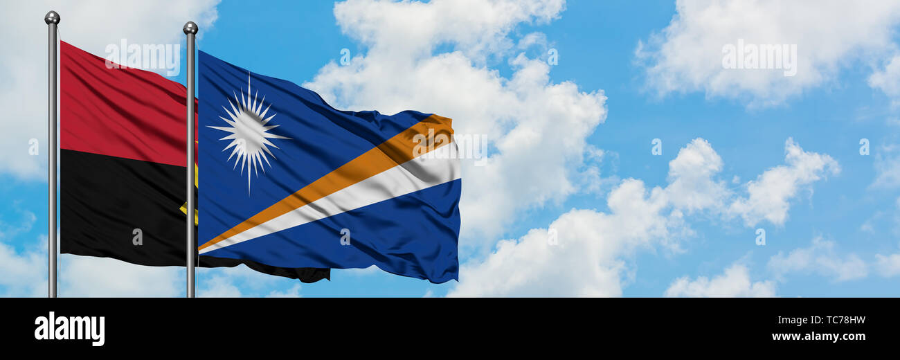 Angola and Marshall Islands flag waving in the wind against white cloudy blue sky together. Diplomacy concept, international relations. - Stock Image
